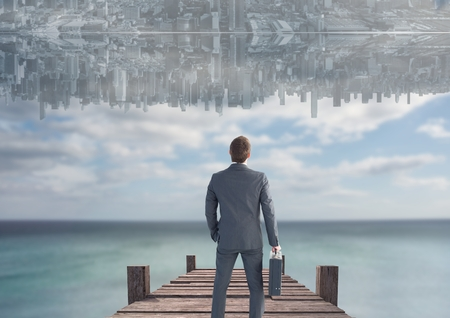 man looking out: Digital composite of up side down city in the sky over the sea with dock. Men looking up.