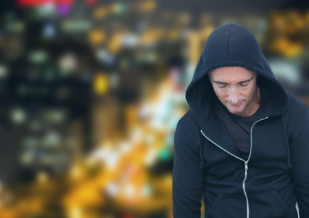 Digital composite of Criminal in hood in front of night city Stock Photo