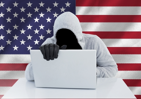 intruding: Digital composite of Anonymous Criminal in hood with laptop in front of American flag Stock Photo