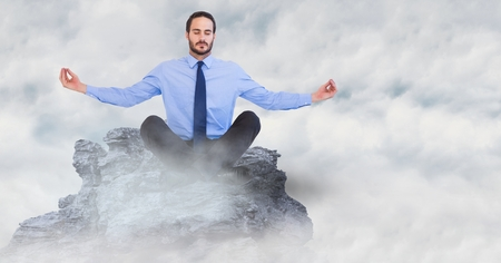 man meditating: Digital composite of Business man meditating on mountain peak in the clouds