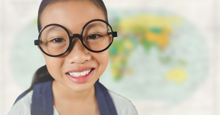 Digital composite of Girl with glasses smiling against blurry map