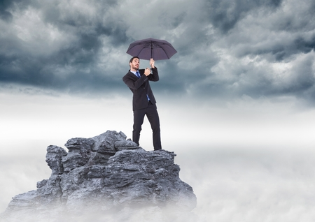 Digital composite of Business man standing on mountain peak with umbrella against stormy clouds Stock Photo