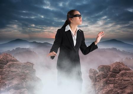 Digital composite of Business woman blindfolded walking on misty mountain peak