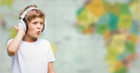Digital composite of Boy with headphones against blurry map