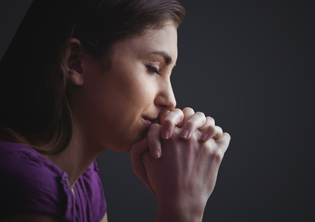 jehovah: Digital composite of Woman praying against dark grey background