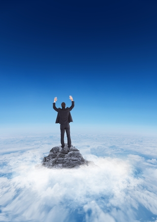 Digital composite of Business man cheering on mountain peak in the clouds