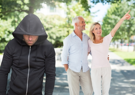 Digital composite of Criminal in hood in front of couple walking in park