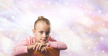 Digital composite of Cute girl sitting against abstract background Stock Photo