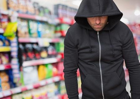 Digital composite of Criminal in hood in shop store