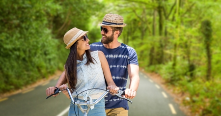 Digital composite of Loving couple riding bicycle during summer vacation Stock Photo