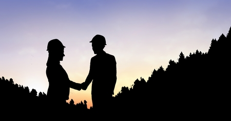 business meeting: Digital composite of Silhouette business people shaking hands on mountain during sunset Stock Photo