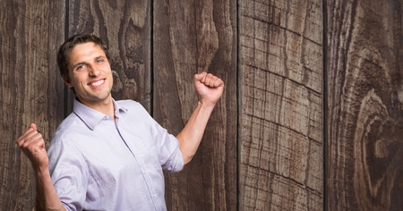 Digital composite of Happy businessman celebrating success against wooden wall
