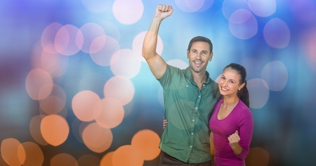 Digital composite of Happy couple celebrating success over bokeh