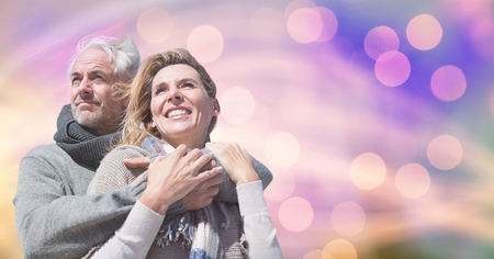 Digital composite of Happy couple in warm clothing against bokeh Stock Photo