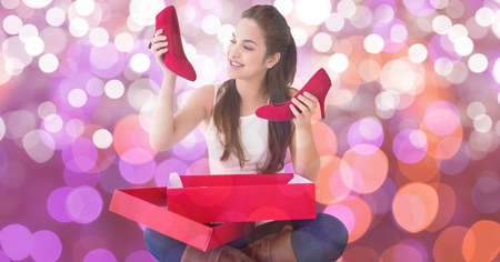 Digital composite of Happy woman looking at new red shoes over bokeh Stock Photo