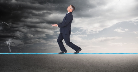 Digital composite of Digital composite image of businessman walking on rope during thunder storm Stock Photo