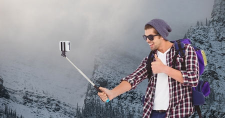 Digital composite of Happy man taking selfie on smart phone against snow covered mountain