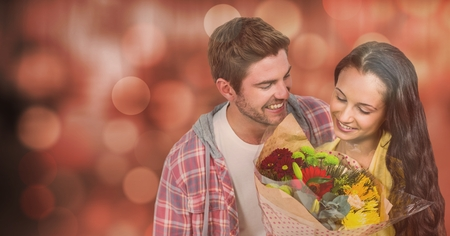 Digital composite of Happy man looking at woman with flowers over bokeh