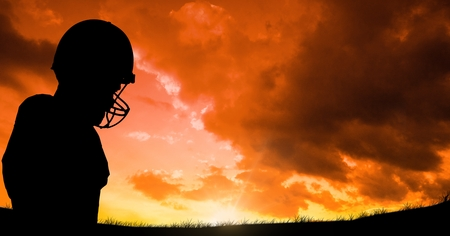 Digital composite of Silhouette player wearing sport helmet against cloudy sky during sunset