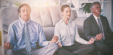 Business people practicing yoga in office Stock Photo
