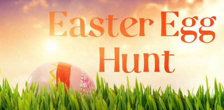 Grass growing outdoors against painted easter eggs on white background Stock Photo