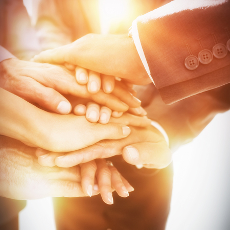 Business team stacking hands together in office Stock Photo
