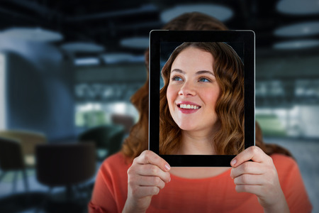 Woman holding digital tablet in front of her face against college Stock Photo