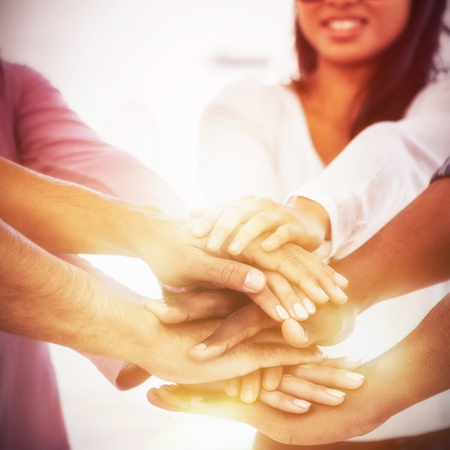 Businesswoman stacking hands with team while standing at creative office Stock Photo