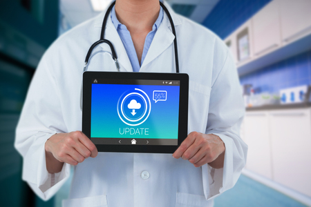 Midsection of female doctor holding digital tablet against update text with download symbol on screen 免版税图像