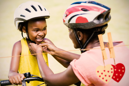 Hearts on line against mother clasping her daughters bicycle helmet Stock Photo