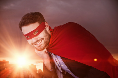 Portrait of smiling businessman pretending to be super hero against office buildings in city during sunset Stock Photo