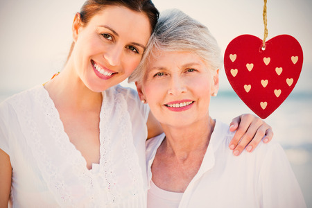 Cute heart decoration against smiling daughter with her mother Stock Photo