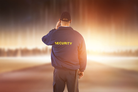 Rear view of security officer listening to earpiece against city on the horizon Stock Photo