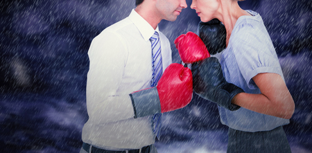 Business people wearing and boxing red gloves against gloomy sky Stock Photo