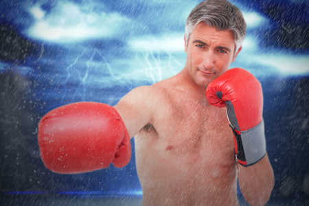 Fit man punching with boxing gloves against thunderstorm over landscape