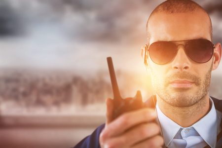 Portrait of security officer talking on walkie talkie against cityscape Stock Photo