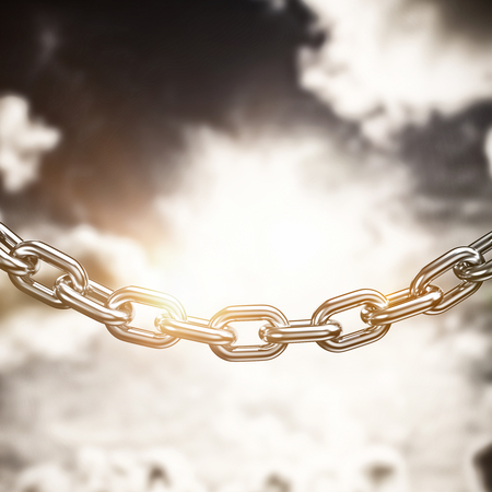 3d image of linked chain against dark sky with white clouds Stock Photo