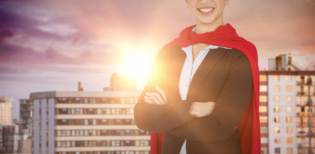 Portrait of confident woman wearing red cape against office buildings in city during sunset Stock Photo