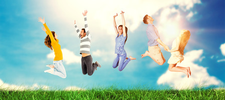 Happy friends jumping against blue sky Stock Photo