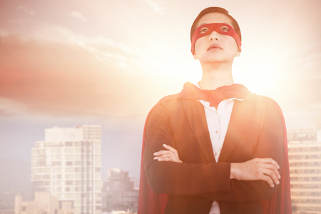 Confident woman pretending to be super hero against buildings in city against blue sky