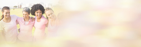 Laughing women wearing pink for breast cancer in park Stock Photo