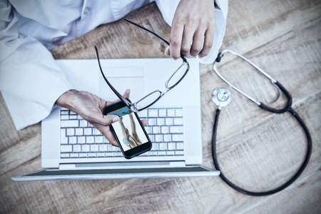 Woman with leg injury against doctor using smartphone on wooden desk Stock Photo