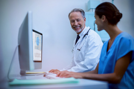 Human skeleton with various medical information against smiling male doctor with nurse Stock Photo