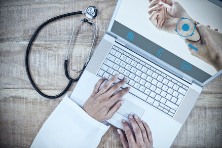 Woman with hand injury against doctor using laptop on wooden desk Stock Photo