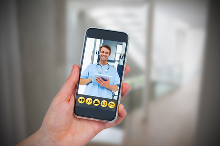 Hand holding mobile phone against white background against wheelchair in the corridor