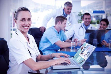 team from behind: Beautiful smiling doctor typing on keyboard with her team behind against uniformed doctor analyzing the brain
