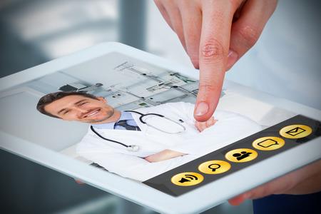Hands using digital tablet against white background against sterile bedroom Standard-Bild