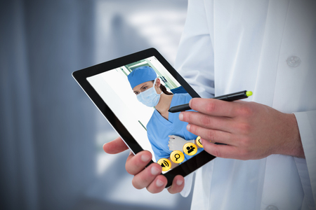 Doctor using digital tablet against wheelchair in the corridor Stock Photo