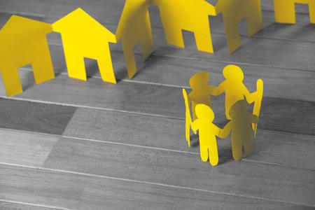 Hoge hoekmening van papieren figuren en huizen op houten tafel Stockfoto