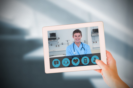 Masculine hand holding tablet against sterile bedroom